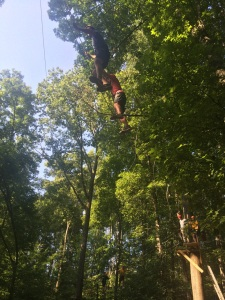Men's Golf members balance on a tight rope across the tree tops.